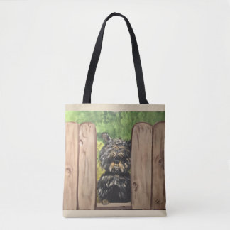Tote with cute dog peeking between fence slats