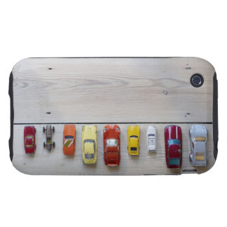 Toy cars lined up in a row on floor tough iPhone 3 cover