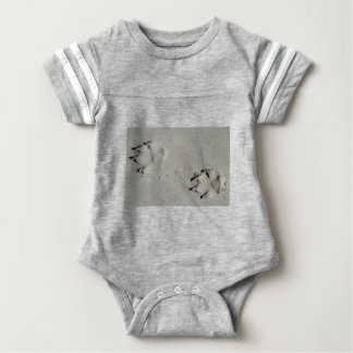 Tracks of a big dog on the sand baby bodysuit