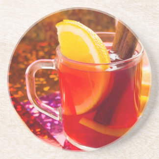 Transparent cup of tea with citrus and cinnamon coaster