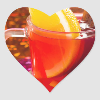 Transparent cup of tea with citrus and cinnamon heart sticker