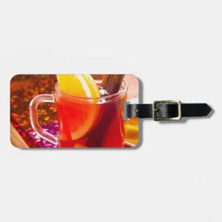 Transparent cup of tea with citrus and cinnamon luggage tag