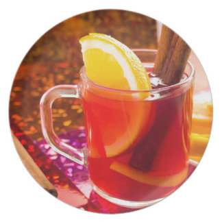 Transparent cup of tea with citrus and cinnamon party plate