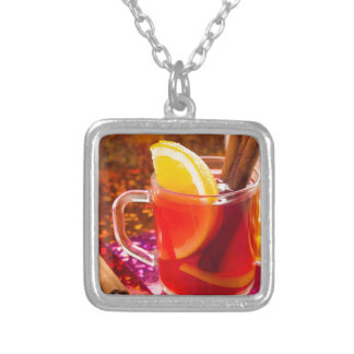 Transparent cup of tea with citrus and cinnamon silver plated necklace