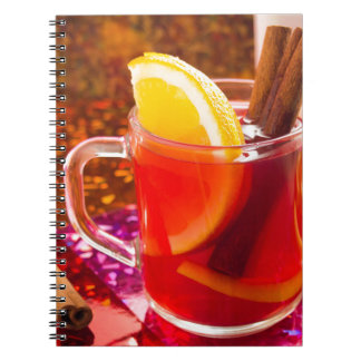Transparent cup of tea with citrus and cinnamon spiral notebook