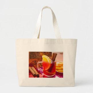 Transparent cup of tea with citrus, cinnamon large tote bag