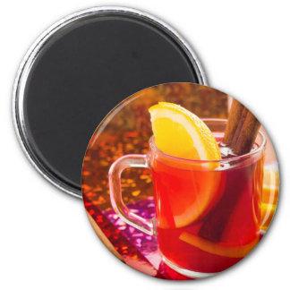 Transparent cup of tea with citrus, cinnamon magnet