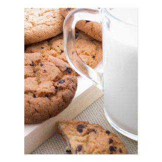Transparent cup with milk and oatmeal cookies letterhead