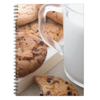 Transparent cup with milk and oatmeal cookies notebook