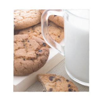 Transparent cup with milk and oatmeal cookies notepad