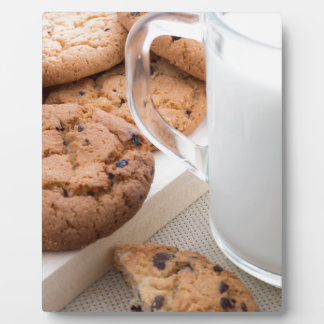 Transparent cup with milk and oatmeal cookies plaque