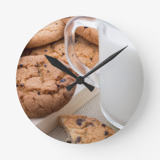 Transparent cup with milk and oatmeal cookies round clock