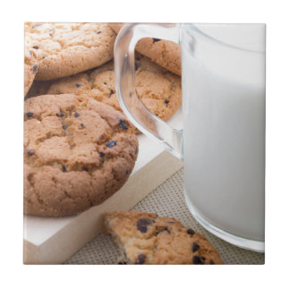 Transparent cup with milk and oatmeal cookies tile