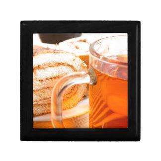 Transparent glass mug with hot tea and chocolate gift box