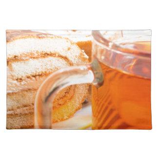 Transparent glass mug with hot tea and chocolate placemat