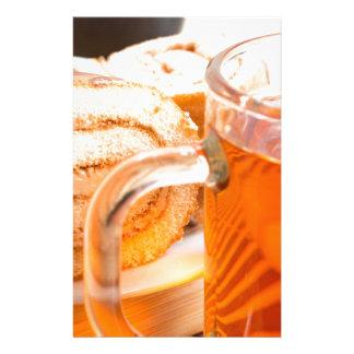Transparent glass mug with hot tea and chocolate stationery