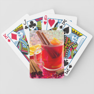 Transparent mug with citrus mulled wine, cinnamon bicycle playing cards