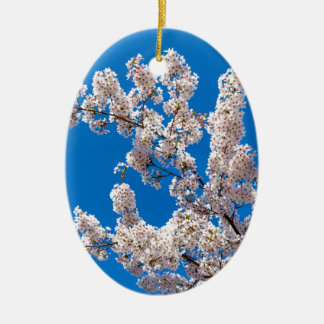 Tree branches with blooming white flowers ceramic oval ornament