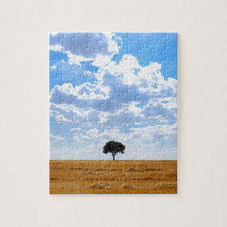 Tree in an harvested wheat field jigsaw puzzle