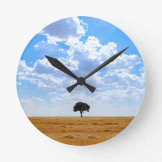 Tree in an harvested wheat field round clock