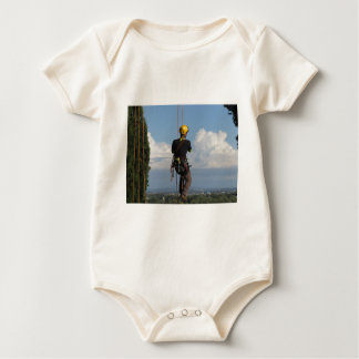 Tree surgeon lumberjack hanging from a big tree baby bodysuit