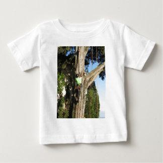 Tree surgeon lumberjack hanging from a big tree baby T-Shirt