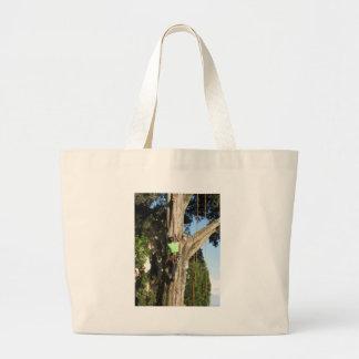 Tree surgeon lumberjack hanging from a big tree large tote bag
