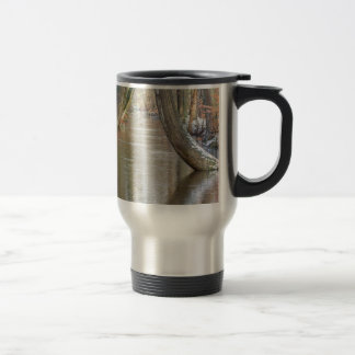 Tree trunks and forest stream  with snow in winter travel mug