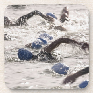 Triathletes competing in swim leg of triathlon. coaster