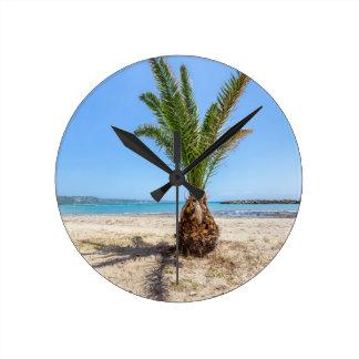 Tropical palm tree on sandy beach wall clock