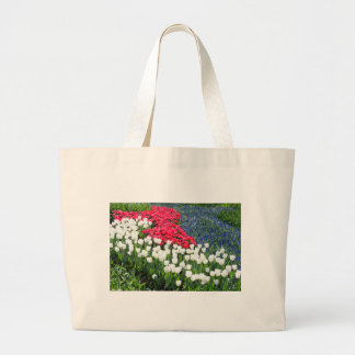 Tulips field in red and white with blue hyacinths large tote bag