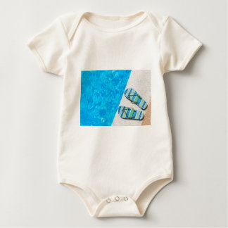 Two bathing slippers on edge of swimming pool baby bodysuit