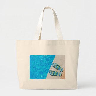 Two bathing slippers on edge of swimming pool large tote bag