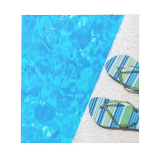 Two bathing slippers on edge of swimming pool notepads