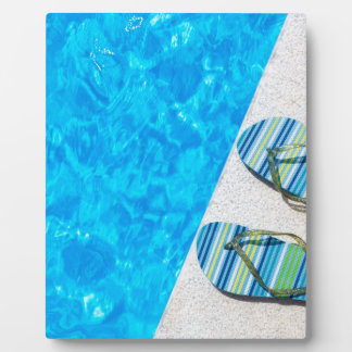 Two bathing slippers on edge of swimming pool plaque