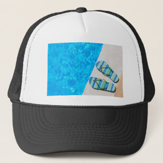 Two bathing slippers on edge of swimming pool trucker hat