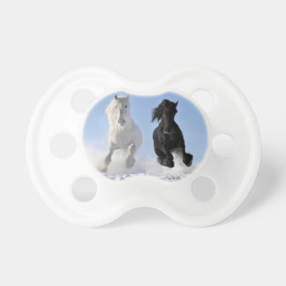 Two beautiful horses black and white run in  snow pacifiers
