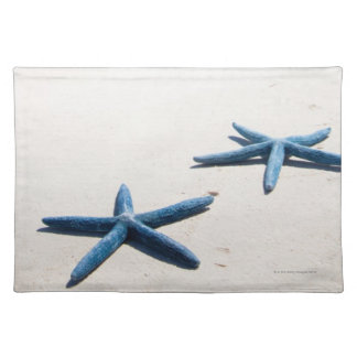 Two blue starfish at water's edge on tropical placemat