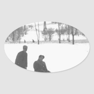 Two Boys Pulling Two Girls on Sleds Oval Sticker