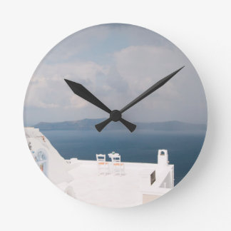 Two chairs on Santorini island Round Clock