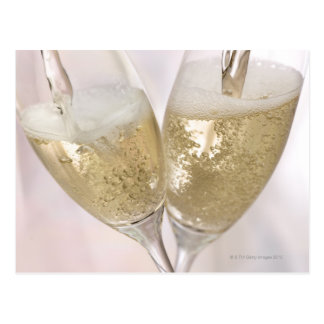 Two champagne flutes being filled with sparkling postcard