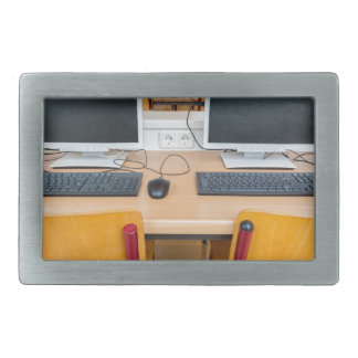 Two computers in classroom on high school belt buckle