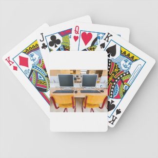 Two computers in classroom on high school bicycle playing cards