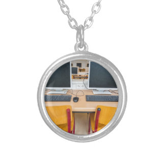 Two computers in classroom on high school silver plated necklace