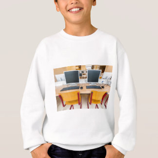 Two computers in classroom on high school sweatshirt