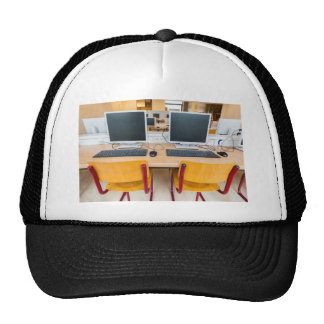 Two computers in classroom on high school trucker hat