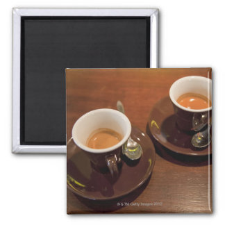 two cups of freshly brewed espresso coffee on a square magnet