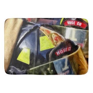 Two Fire Helmets And Fireman's Jacket Bath Mat