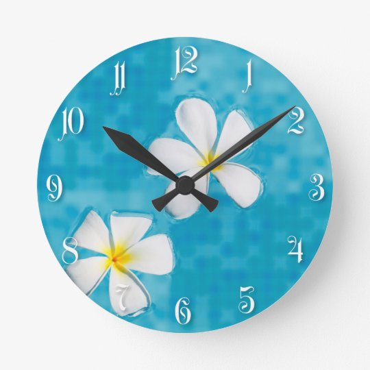 Two frangipani flowers in a blue water clocks