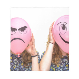 Two girls holding pink balloons with expressions notepads